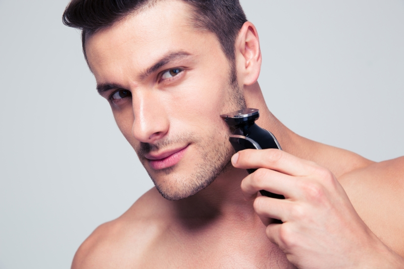 12232323-young-man-shaving-with-electric-razor
